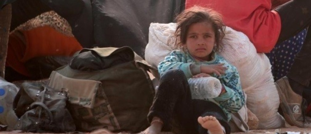 A refugee girl rests, among Iraqi refugees that fled violence in Mosul and internally displaced Syrians whom fled Islamic State controlled areas in Deir al-Zor, near the Iraqi border