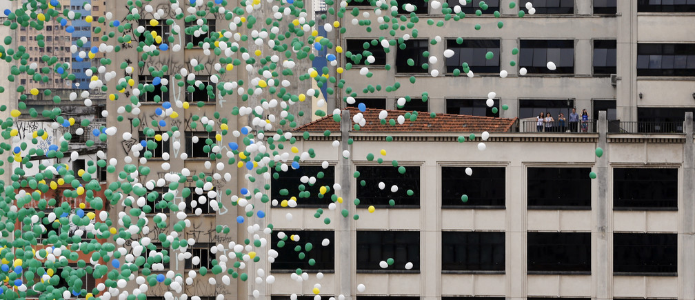 Residents watch from a building balloons are released into the skies above Sao Paulo downtown during year end celebrations December 30, 2013. REUTERS/Paulo Whitaker (BRAZIL - Tags: SOCIETY) - GM1E9CU1TA701