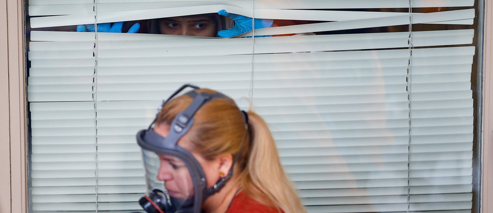 A Servpro cleaning crew member peeks through window blinds at Life Care Center of Kirkland, a long-term care facility linked to several confirmed coronavirus cases, in Kirkland, Washington, U.S. Coronavirus china virus health healthcare who world health organization disease deaths pandemic epidemic worries concerns Health virus contagious contagion viruses diseases disease lab laboratory doctor health dr nurse medical medicine drugs vaccines vaccinations inoculations technology testing test medicinal biotechnology biotech biology chemistry physics microscope research influenza flu cold common cold bug risk symptomes respiratory china iran italy europe asia america south america north washing hands wash hands coughs sneezes spread spreading precaution precautions health warning covid 19 cov SARS 2019ncov wuhan sarscow wuhanpneumonia  pneumonia outbreak patients unhealthy fatality mortality elderly old elder age serious death deathly deadly