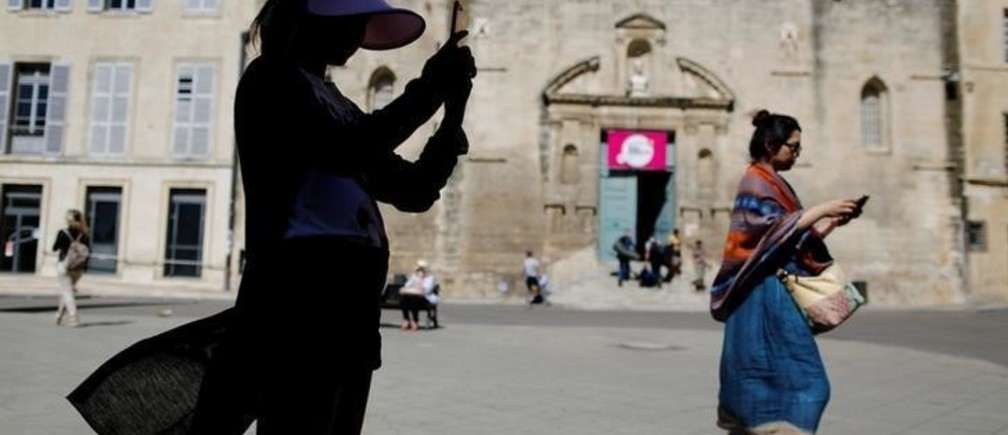 People use their mobile phones in downtown Arles, France July 3, 2017. REUTERS/Tony Gentile