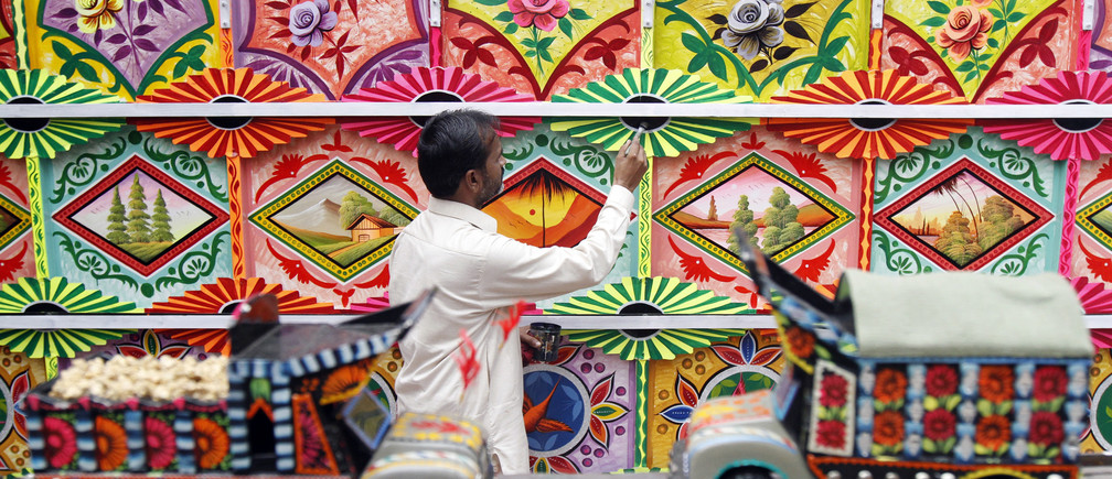A Muslim artist from Pakistan paints a platform for the Hindu Durga Puja festival