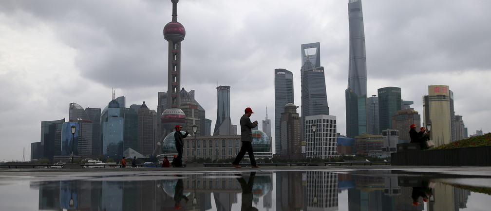 People walk on the bund in front of the financial district of Pudong in Shanghai, China March 9, 2016. REUTERS/Aly Song - GF10000338954