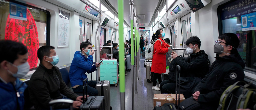 Passengers wearing face masks ride a subway train on the first day the city's subway services resumed following the novel coronavirus disease (COVID-19) outbreak, in Wuhan of Hubei province, the epicentre of China's coronavirus outbreak, March 28, 2020. REUTERS/Aly Song - RC2SSF9A3QMB