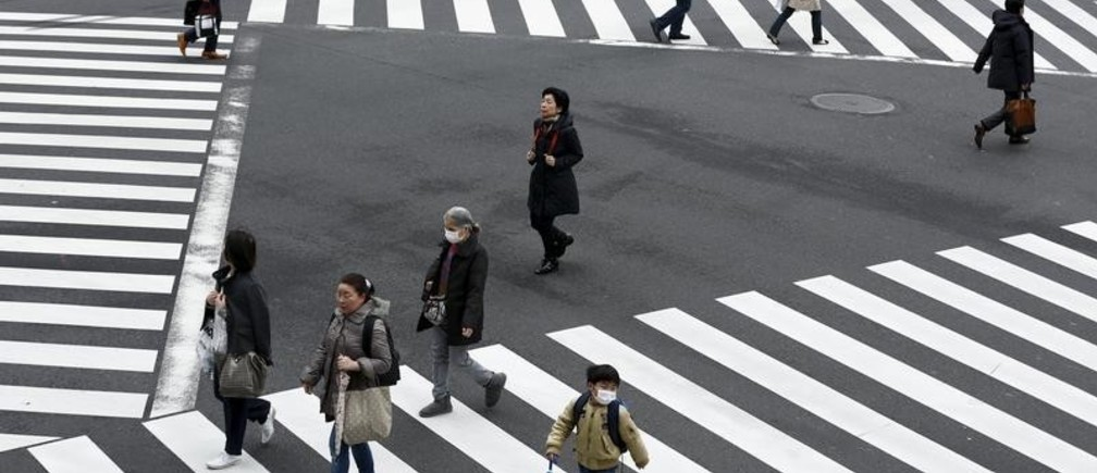 People cross a street in the Ginza shopping district in Tokyo, Japan, March 24, 2016. Japan's consumer inflation was flat in the year to February as low energy costs and weak consumption put a lid on price growth, keeping the central bank under pressure to top up stimulus even after easing policy less than two months ago. REUTERS/Thomas Peter - GF10000359724