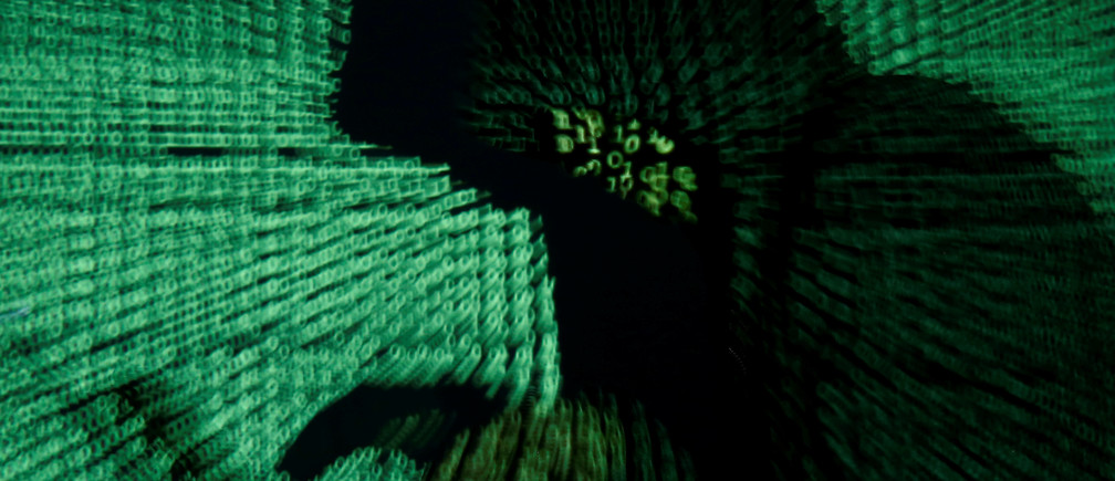 A man holds a laptop computer as cyber code is projected on him in this illustration picture taken on May 13, 2017. Capitalizing on spying tools believed to have been developed by the U.S. National Security Agency, hackers staged a cyber assault with a self-spreading malware that has infected tens of thousands of computers in nearly 100 countries. REUTERS/Kacper Pempel/Illustration - RTX35OS3
