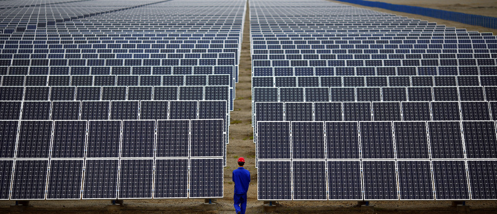 A worker inspects solar panels at a solar Dunhuang, 950km (590 miles) northwest of Lanzhou, Gansu Province September 16, 2013. China is pumping investment into wind power, which is more cost-competitive than solar energy and partly able to compete with coal and gas. China is the world's biggest producer of CO2 emissions, but is also the world's leading generator of renewable electricity. Environmental issues will be under the spotlight during a working group of the Intergovernmental Panel on Climate Change, which will meet in Stockholm from September 23-26. REUTERS/Carlos Barria (CHINA - Tags: ENERGY BUSINESS ENVIRONMENT) - GM1E99M16HZ01