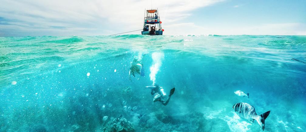 Buceador submarino y barco de pesca sobre el Mar Caribe en Cozumel, México