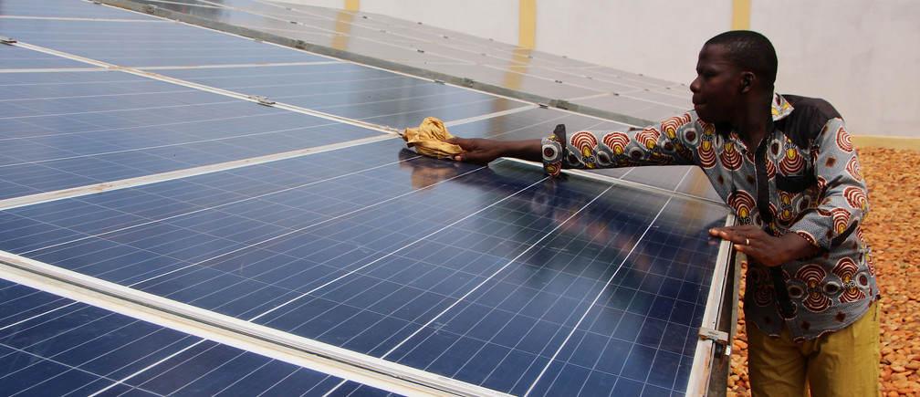 A technician cleans solar panels, part of the BBOXX and EDF solar energy system used to provide electricity to Sikpe Afidegnon village, Togo May 16, 2019. Picture taken May 16, 2019. REUTERS/Noel Kokou Tadegnon