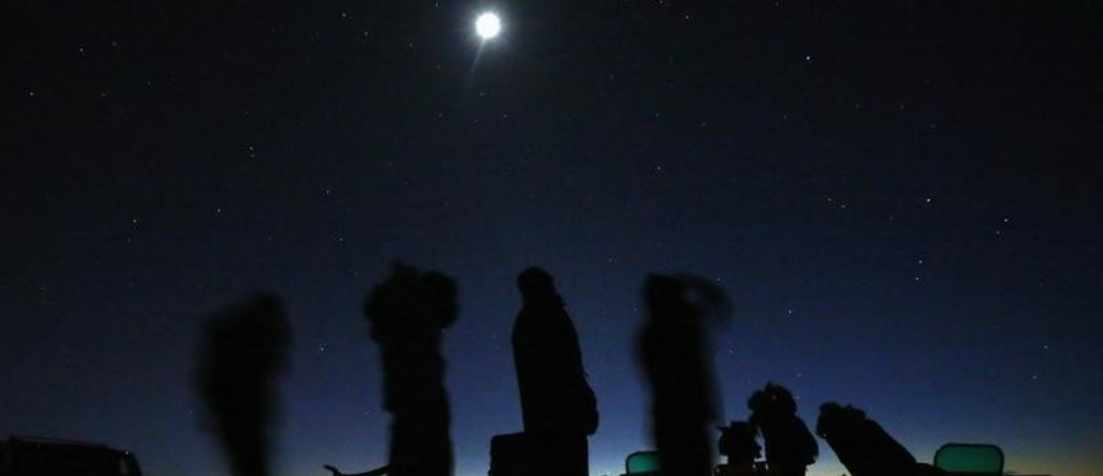 The moon shines above a group of people on an Unidentified Flying Object (UFO) tour in the desert outside Sedona, Arizona February 14, 2013. Picture taken February 14, 2013.    REUTERS/Mike Blake   (UNITED STATES - Tags: SCIENCE TECHNOLOGY ENVIRONMENT SOCIETY) - GM1E9310K7001