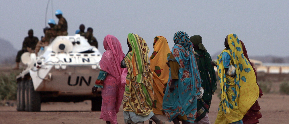 Displaced Sudanese women walk past an armoured personnel carrier (APC) of United Nations-African Union Mission in Nyala, southern Darfur March 17,2009. Law and order have collapsed in Darfur where international experts say at least 200,000 people have been killed, while Khartoum says 10,000 have died. The undermanned peacekeeping force has found itself caught in the middle of an increasingly chaotic conflict involving bandits, rival tribes, government militias and rebels. REUTERS/Zohra Bensemra (SUDAN POLITICS CONFLICT SOCIETY IMAGE OF THE DAY TOP PICTURE) FOR BEST QUALITY IMAGE ALSO SEE: GF10000151114 - GM1E53I07P501