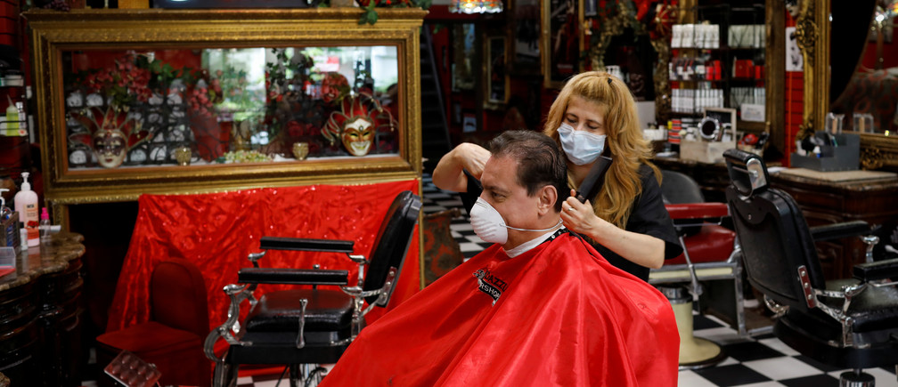 A hairdresser wearing a protective mask cuts the hair of a man at a barber shop, as Miami-Dade County eases some of the lockdown measures put in place during the coronavirus disease (COVID-19) outbreak, in Miami, Florida, U.S., May 18, 2020. REUTERS/Marco Bello - RC29RG9B5CG4