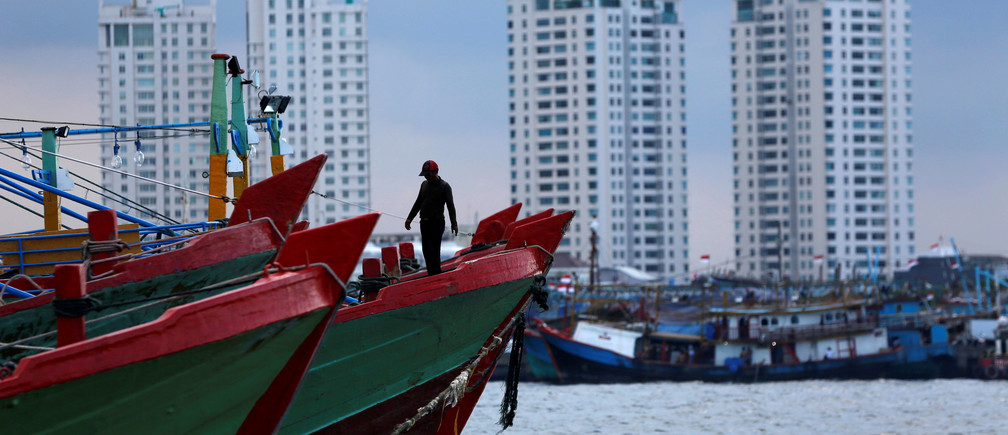A worker walks on top of wooden boat  at Muara Baru port in Jakarta December 8, 2014. REUTERS/Beawiharta/File Photo                   GLOBAL BUSINESS WEEK AHEAD PACKAGE - SEARCH 'BUSINESS WEEK AHEAD 31 OCT'  FOR ALL IMAGES - RTX2R4R2
