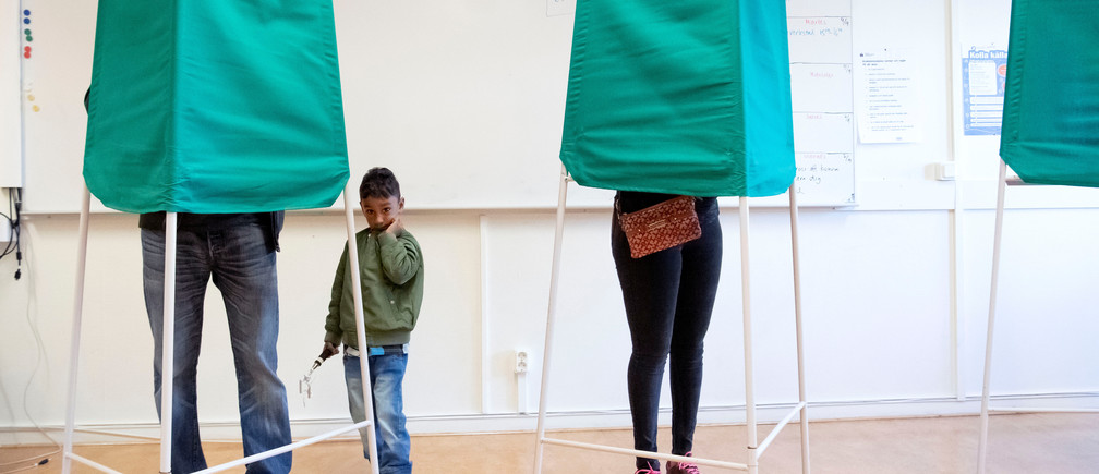 A child looks on as people stand in voting booths, in Malmo, Sweden September 9, 2018. TT News/Johan Nilsson via REUTERS ATTENTION EDITORS - THIS IMAGE WAS PROVIDED BY A THIRD PARTY. SWEDEN OUT. NO COMMERCIAL OR EDITORIAL SALES IN SWEDEN. - RC1F763E53C0