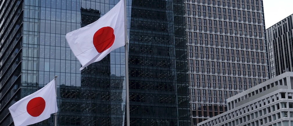 Japanese national flags flutter in front of buildings at Tokyo's business district in Japan, February 22, 2016. Growth in Japan's manufacturing activity slowed sharply in February as new export orders contracted at the fastest pace in three years, a worrying sign that overseas demand is deteriorating rapidly as China's economy slows, a preliminary survey showed on Monday.    REUTERS/Toru Hanai       TPX IMAGES OF THE DAY      - GF10000318199