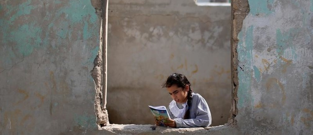 A Palestinian UNRWA schoolgirl holds her book as she stands by a window outside her family home in Al-Shati refugee camp in Gaza City October 23, 2019. Picture taken October 23, 2019. REUTERS/Mohammed Salem     TPX IMAGES OF THE DAY - RC2N5D9JF9UC
