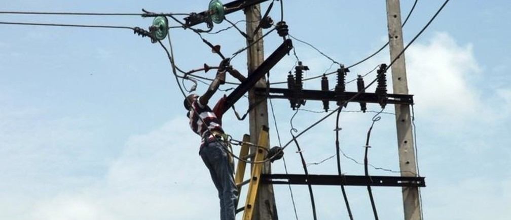 A power official works on an electric pole along a street in Nigeria's commercial capital Lagos October 3, 2012.REUTERS/Akintunde Akinleye(NIGERIA - Tags: ENERGY SOCIETY)