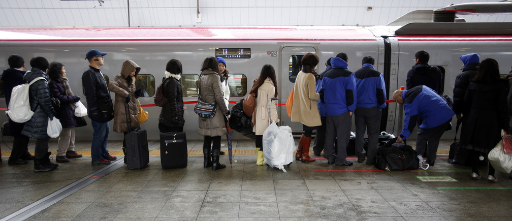 People line up in front of a bullet train at a platform in Tokyo Station as the bullet train service is suspended due to heavy snowfall in Tokyo February 15, 2014. REUTERS/Yuya Shino (JAPAN - Tags: ENVIRONMENT TRANSPORT) - GM1EA2F0TLM01