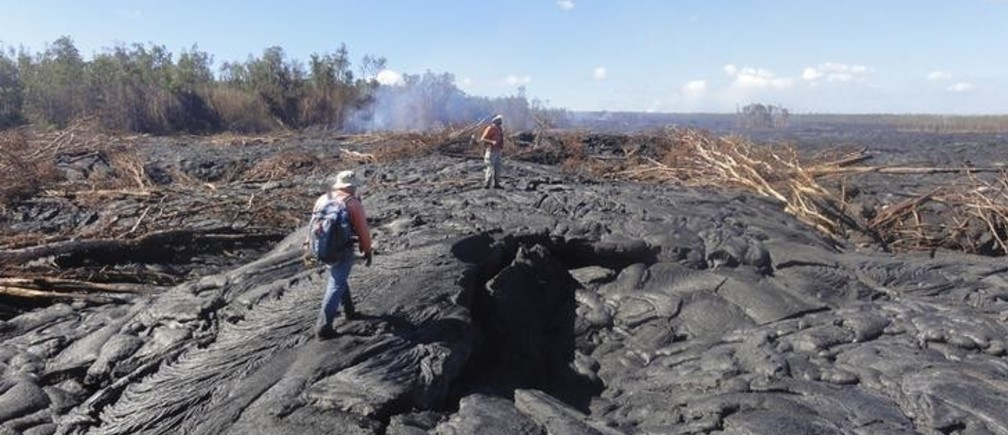 Hawaii Volcano Observatory (HVO) geologists walk over the surface of a lava flow from the Kilauea Volcano to track surface breakouts near the village of Pahoa, Hawaii October 22, 2014.  The lava began flowing from the Kilauea Volcano on June 27 and as of October 24 the flow front was 0.7 miles (1.2 km) from Pahoa Village Road, according to the U.S. Geological Survey.  About 4,000 people overall live in the residential communities that the lava is approaching. Picture taken October 22, 2014.  REUTERS/U.S. Geological Survey/Handout  (UNITED STATES - Tags: ENVIRONMENT DISASTER) THIS IMAGE HAS BEEN SUPPLIED BY A THIRD PARTY. IT IS DISTRIBUTED, EXACTLY AS RECEIVED BY REUTERS, AS A SERVICE TO CLIENTS. FOR EDITORIAL USE ONLY. NOT FOR SALE FOR MARKETING OR ADVERTISING CAMPAIGNS