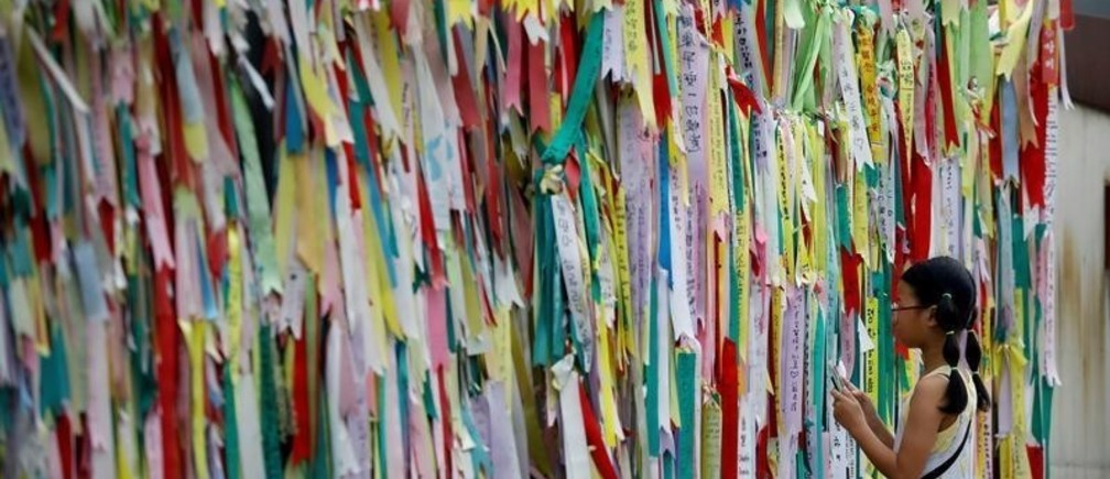A girl looks at a barbed-wire fence decorated with ribbons bearing messages wishing for the unification between the two Koreas near the demilitarized zone separating the two Koreas in Paju, South Korea, August 10, 2017.  REUTERS/Kim Hong-Ji     TPX IMAGES OF THE DAY - RC1DEE456B70