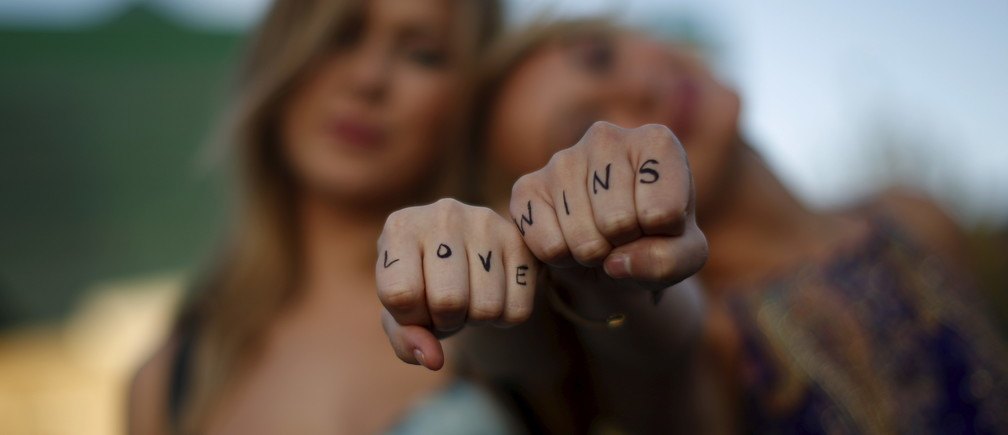 """Cherilyn Wilson, 26, (L) and Chelsea Kane, 26, display their fists, with the message """"Love Wins"""" written on them, as they pose at a celebration rally in West Hollywood, California, United States, June 26, 2015. The U.S. Supreme Court ruled on Friday that the U.S. Constitution provides same-sex couples the right to marry in a historic triumph for the American gay rights movement."""