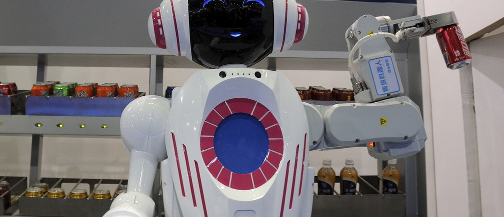 A sales assistant robot picks up a can of Coca Cola during a demonstration at the World Robot Conference in Beijing, China, November 24, 2015. The conference, which kicked off in Beijing on Monday, is a three-day event including a forum, an exhibition and a robot contest for youth, Xinhua News Agency reported. Picture taken November 24, 2015. REUTERS/Stringer CHINA OUT. NO COMMERCIAL OR EDITORIAL SALES IN CHINA  - RTX1VPX3