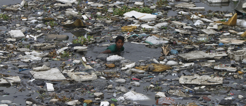 A boy searches for fish in the polluted sea backwaters near marina beach in the southern Indian city of Chennai July 3, 2013. REUTERS/Babu (INDIA - Tags: SOCIETY ENVIRONMENT) - GM1E9731O7D01