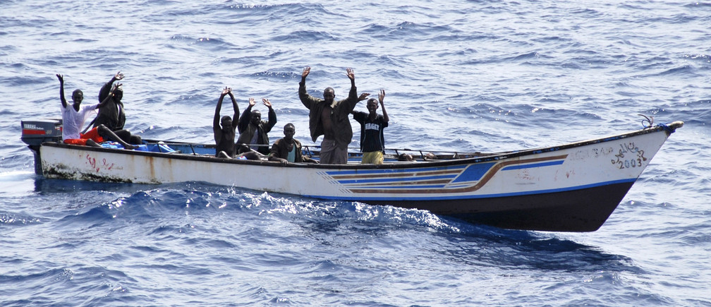 Suspected Somali pirates raise their hands in their skiff during their arrest by Marines from NATO's Portuguese frigate Corte-Real in the Gulf of Aden June 22, 2009. Eight Somali pirates armed with rocket-propelled grenades and AK-47s were caught in a high-speed chase by the NATO alliance's Portuguese warship Corte-Real after they tried to attack a merchant vessel in the Gulf of Aden. Picture taken June 22, 2009. REUTERS/NATO/Carlos Dias/Handout (GULF OF ADEN CONFLICT CRIME LAW POLITICS) FOR EDITORIAL USE ONLY. NOT FOR SALE FOR MARKETING OR ADVERTISING CAMPAIGNS - GM1E56N1GSY01