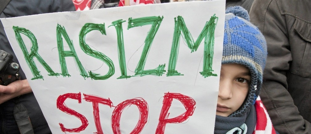"A boy holds a sign which reads ""Racism stop"" during demonstration of members of Muslim community and groups fighting discrimination against Muslims after Paris attacks in Poznan, Poland"