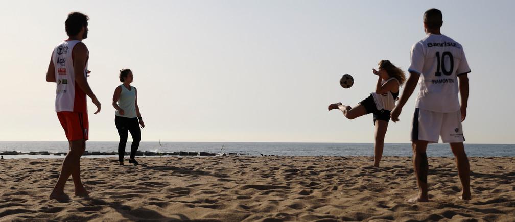 La gente juega mientras disfruta del tiempo soleado en la playa de la Barceloneta en medio de la relajación de las restricciones implementadas para frenar la propagación de la enfermedad coronavirus (COVID-19), en Barcelona, España, el 8 de mayo de 2020.