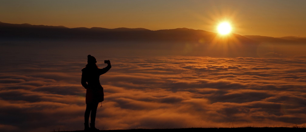 A woman takes a picture with a smartphone on the Smetovi mountain range near Zenica, Bosnia and Herzegovina, December 20, 2015.