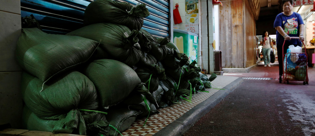 Sandbags are put in front of a shop at Lei Yue Mun, a village as one of the several areas at-risk, as Typhoon Mangkhut approaches Hong Kong, China September 14, 2018. REUTRERS/Bobby Yip - RC12B51BE620
