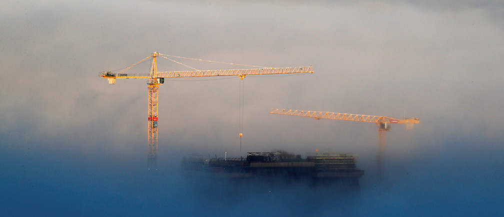 Building cranes and the top of the new Munch Museum are seen above heavy fog in Oslo, Norway November 15, 2017. NTB Scanpix/Cornelius Poppe via REUTERS ATTENTION EDITORS - THIS IMAGE WAS PROVIDED BY A THIRD PARTY. NORWAY OUT. NO COMMERCIAL OR EDITORIAL SALES IN NORWAY - RC1F2D9E65C0