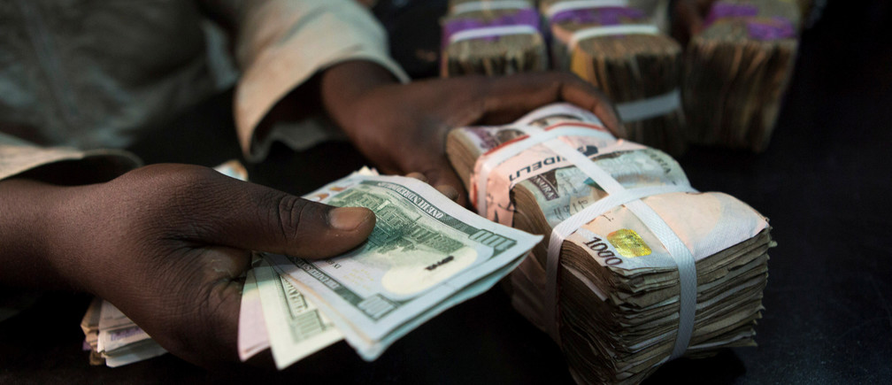 A trader changes dollars with naira at a currency exchange store in Lagos, Nigeria, February 12, 2015.  REUTERS/Joe Penney/File Photo - RTSS1X9