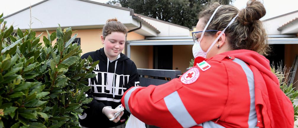 Una voluntaria entrega suministros a las personas que no pueden salir de sus casas.