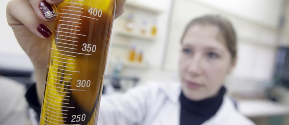 Un ingeniero químico sostiene un tubo de ensayo de biocombustible en una fábrica en Passo Fundo, Brasil.