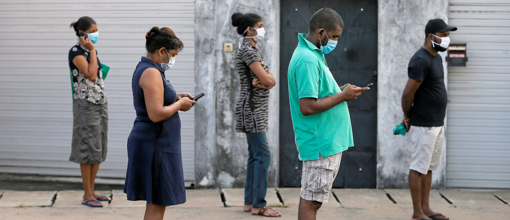 People maintain the one-meter distance in-between each other as they stand in a line to buy groceries at a supermarket during the time government lifted the curfew, as the number of people tested positive for coronavirus disease (COVID-19) in the country increases, in Colombo, Sri Lanka March 24, 2020. REUTERS/Dinuka Liyanawatte     TPX IMAGES OF THE DAY - RC27QF910AWZ