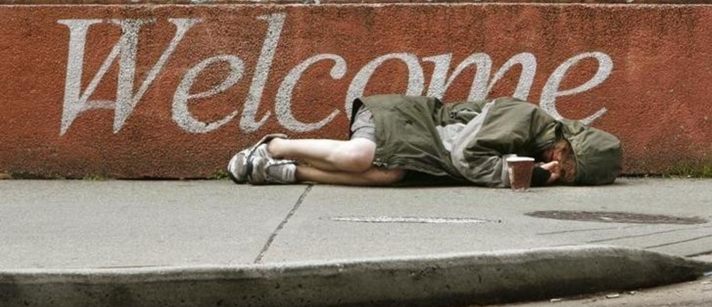 A homeless woman lies on a sidewalk using an empty coffee cup to collect spare change from passers-by in downtown Vancouver, British Columbia June 29, 2007.              REUTERS/Andy Clark     (CANADA)