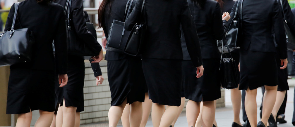 Female office workers wearing high heels, clothes and bags of the same colour make their way at a business district in Tokyo, Japan, June 4, 2019. REUTERS/Kim Kyung-Hoon - RC1A0C81EDF0