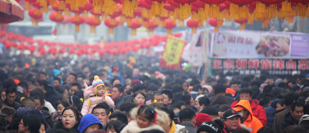 A child sitting on an adult's shoulder is seen among visitors as they flock to a temple fair on Chinese Lantern Festival on the last day of the lunar new year celebrations in Qingdao, Shandong province, China February 19, 2019. REUTERS/Stringer ATTENTION EDITORS - THIS IMAGE WAS PROVIDED BY A THIRD PARTY. CHINA OUT. - RC18E29B1810