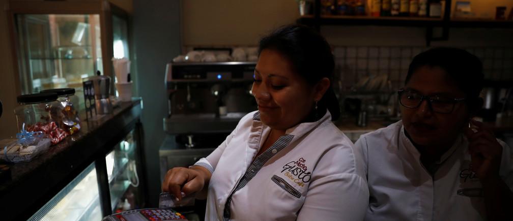 A cashier processes a customer's credit card during payment at a cafe in San Salvador, El Salvador April 4, 2019. REUTERS/Jose Cabezas - RC198CF7D840