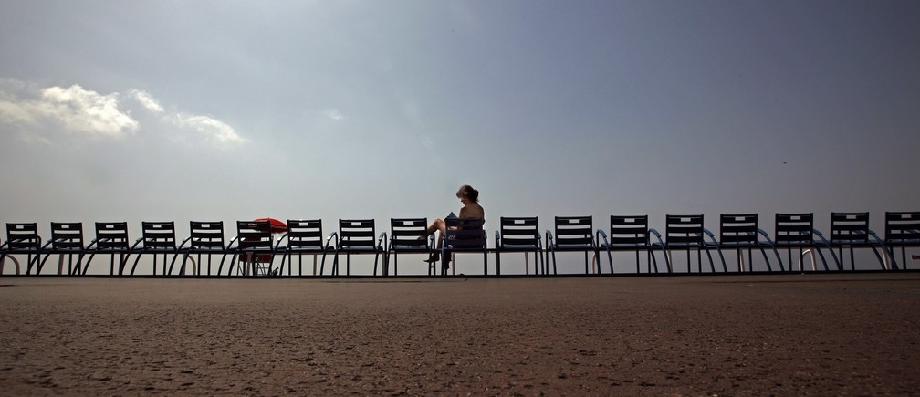 A woman enjoys the sun on the Promenade des Anglais as temperatures are close to 30 degrees Celsius (86 Fahrenheit) in Nice June 29, 2012.  REUTERS/Eric Gaillard (FRANCE - Tags: TRAVEL ENVIRONMENT) - RTR34CCP