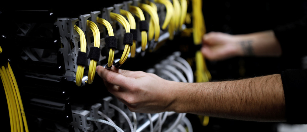 Cables run into the back of a server unit inside the data center of Equinix in Pantin, near Paris, France, December 7, 2016