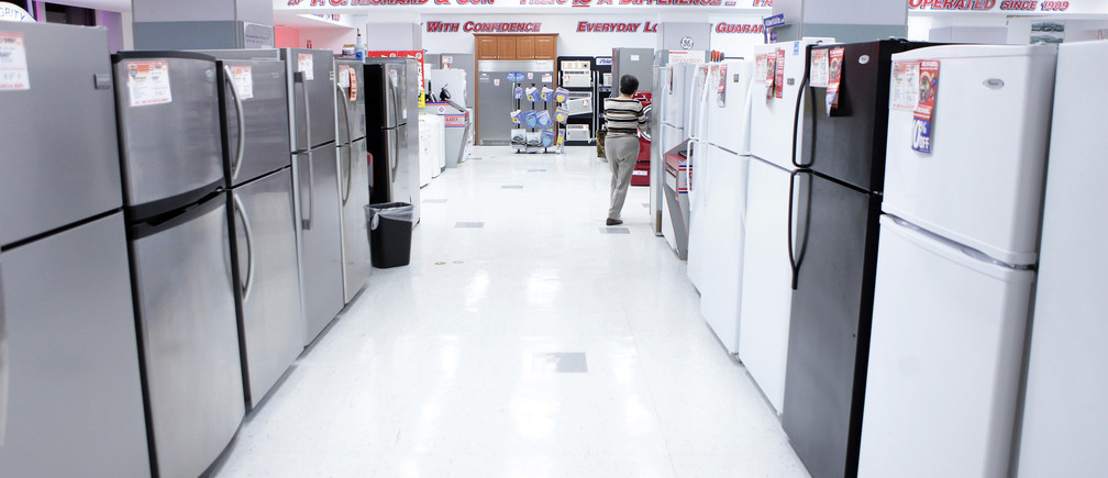 A woman walks through a display of refrigerators at a PC Richard and Son store in New York December 23, 2009.  U.S. consumer spending rose in November as incomes recorded their biggest gain in six months, but a surprise drop in new home sales to a seven-month low was a reminder that the economic recovery would be bumpy. REUTERS/Lucas Jackson (UNITED STATES - Tags: BUSINESS) - RTR28BF7