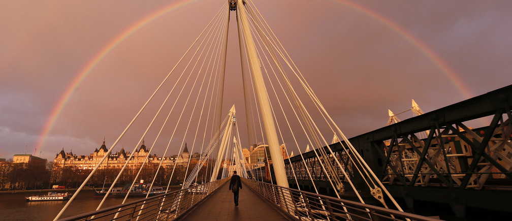 A rainbow appears as a pedestrian crosses one of the Golden Jubilee Bridges in London January 31, 2014.