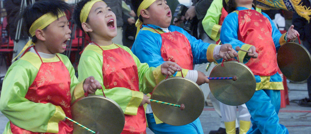 Elementary school students beat gongs January 2, 2001, to celebrate the direct sailing between Taiwan-held Quemoy island and Xiamen on China's southeast coast. Taiwan began historic direct transport links with archrival China on Tuesday as part of efforts to ease tension. - PBEAHULEWAW