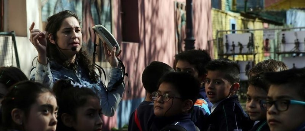 A tour guide speaks to school children in Caminito, a tourist hotspot of La Boca neighborhood, in Buenos Aires, Argentina August 4, 2017. REUTERS/Marcos Brindicci - RC1CD362EAB0