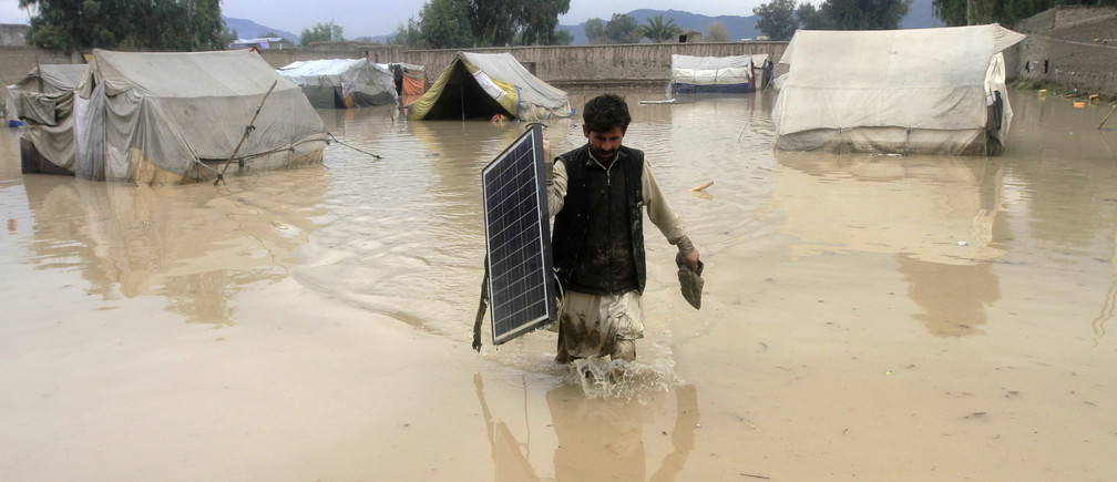 An Afghan man carries a solar panel as he wades through flood waters in the Behsud District of Nangarhar province, February 25, 2015. Four people were killed and hundred houses have been damaged after a heavy rain and flood in Nangarhar province of Afghanistan, the provincial spokesman Ahmadzia Abdulzai said. REUTERS/Parwiz (AFGHANISTAN - Tags: DISASTER ENVIRONMENT TPX IMAGES OF THE DAY) - GM1EB2P1QRM01