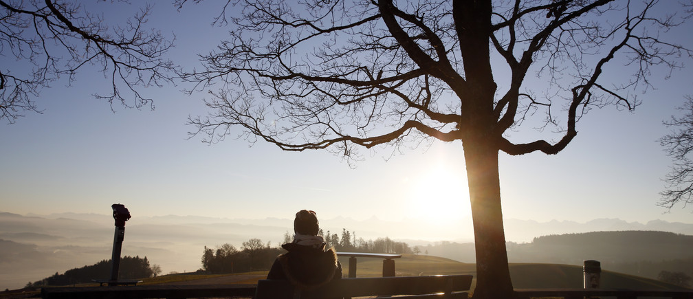 A women sits on a bench on the top of the Gurten mountain in the early morning in Bern, Switzerland December 29, 2015. REUTERS/Ruben Sprich - D1AESEBXMNAA