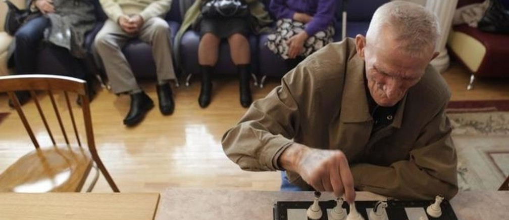 An elderly man takes part in a chess competition at a gerontological center in Stavropol November 25, 2010. Some 40 participants from elderly homes around the region took part in the competition.  REUTERS/Eduard Korniyenko  (RUSSIA - Tags: SPORT CHESS HEALTH SOCIETY)