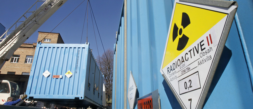 Workers place a container with spent highly-enriched uranium on a truck at a nuclear research facility in Kiev March 24, 2012.